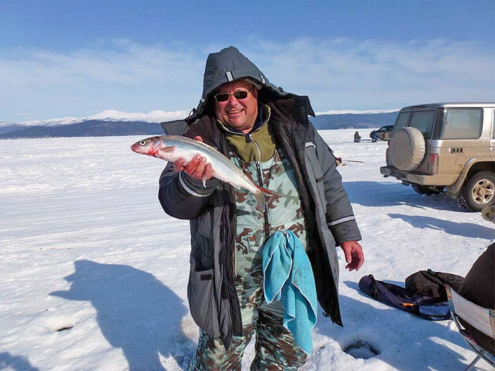 Довольный рыбак с рыбкой в руке