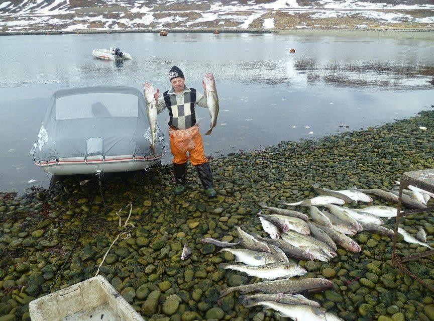 Рыбак на берегу с хорошим уловом