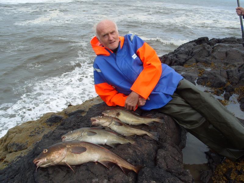 Пожилой рыбак с пойманной рыбой на берегу моря