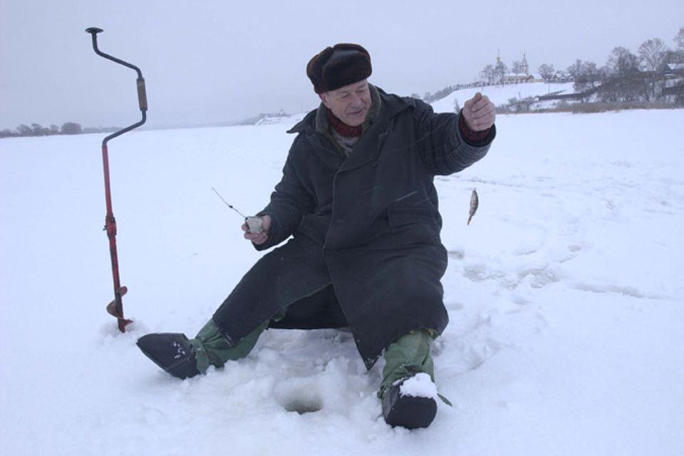 Пожилой рыбак на льду с удочкой