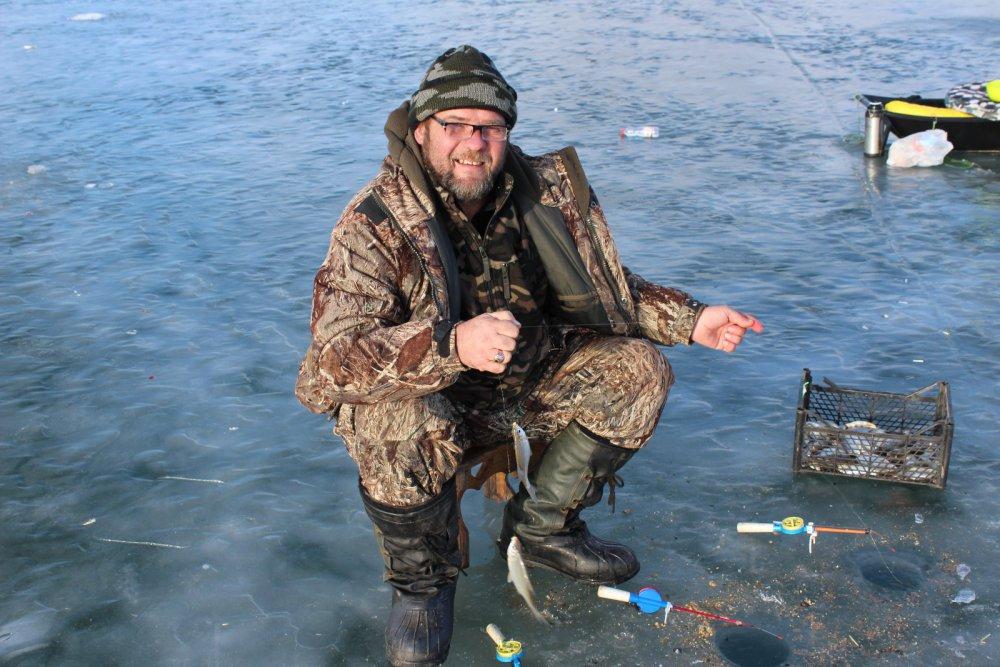 Бородатый мужик на льду с удочкой