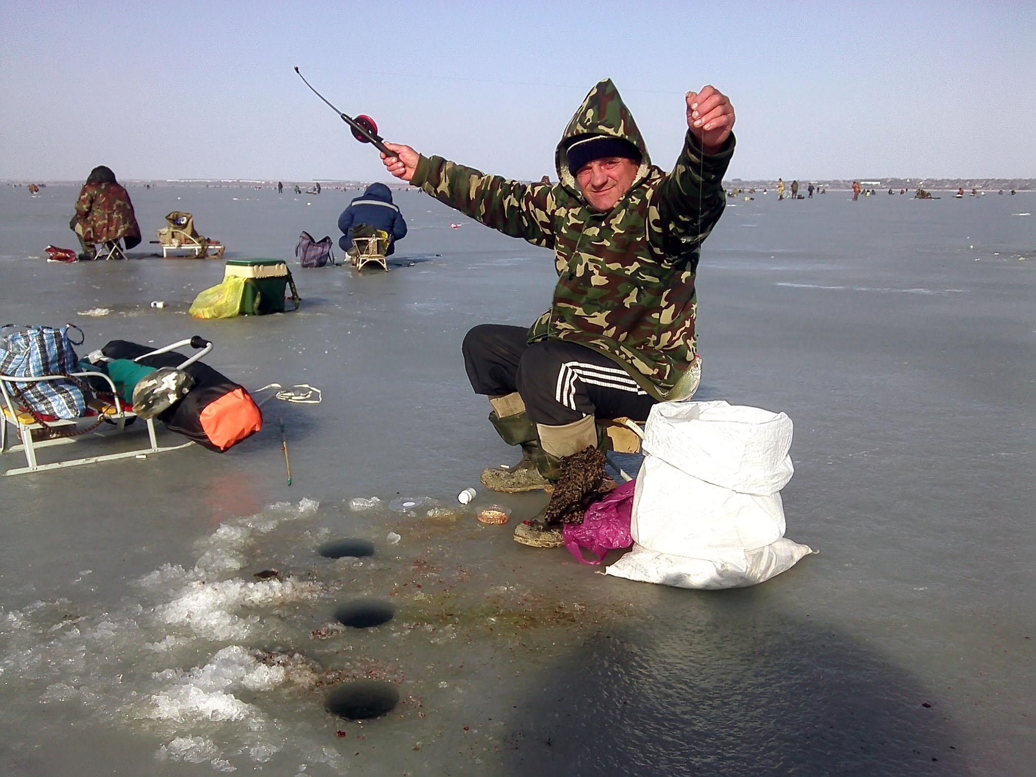 Довольный рыбак на льду