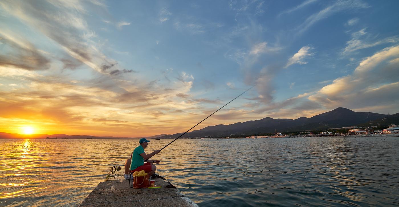 Два рыбака с удочками на закате дня