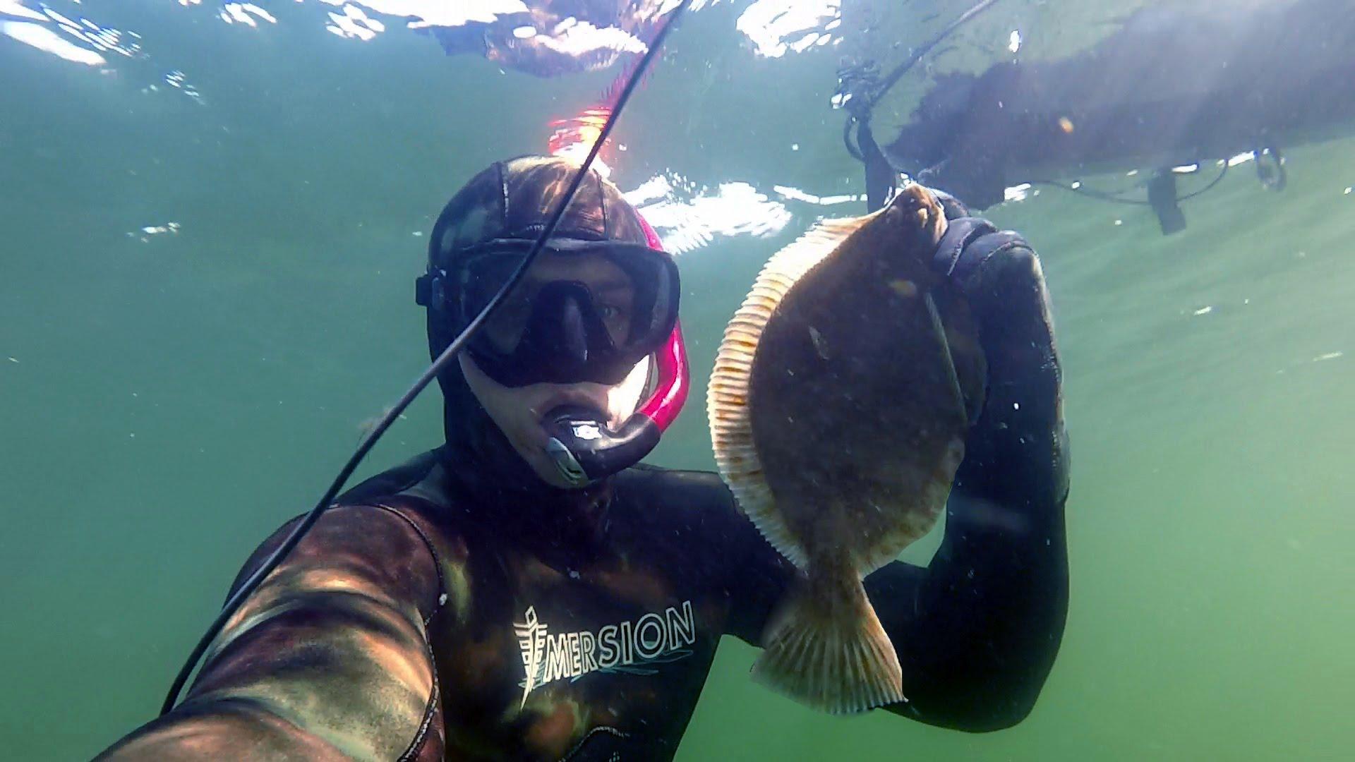 Подводный охотник с камбалой в руках
