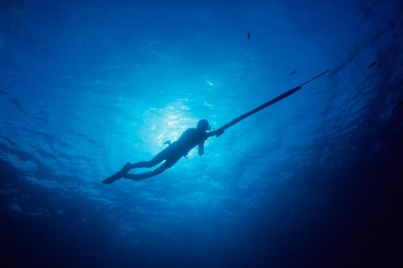 Охотник подводой с длинным ружьем