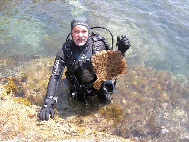 Мужик в акваланге с рыбой в руке