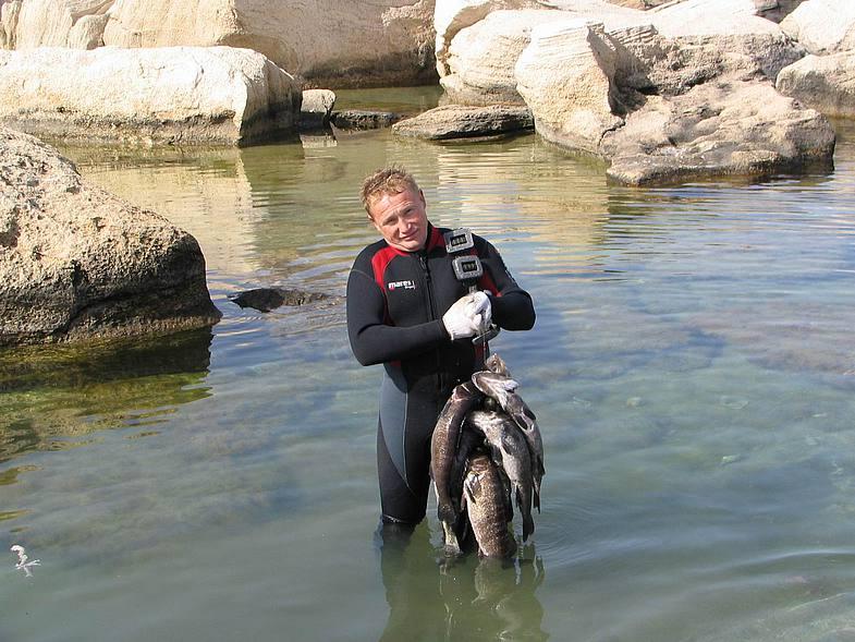 Рыбак в гидро костюме с рыбой в руках