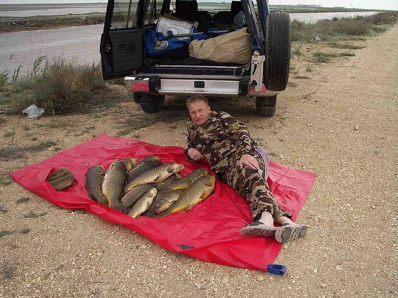 Рыбак лежит с кучей рыбы