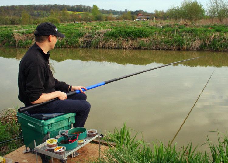 Рыбак с удочкой на берегу реки