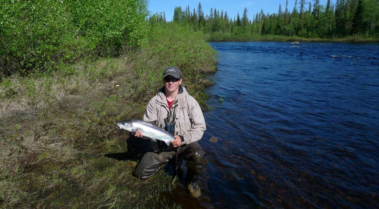 Парень на берегу реки с рыбиной в руках
