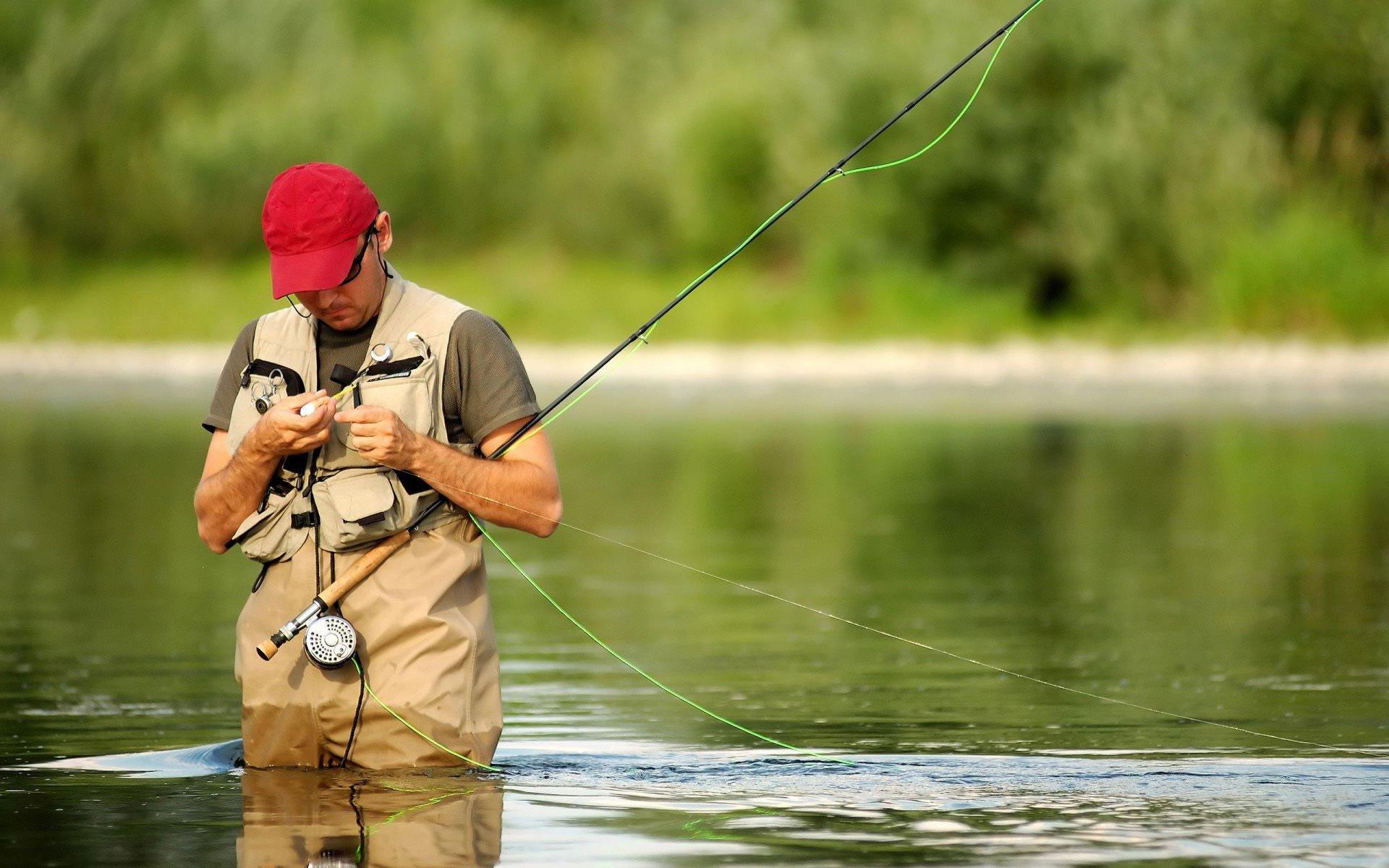 Рыбак стоя в воде  с нахлыстовой удочкой