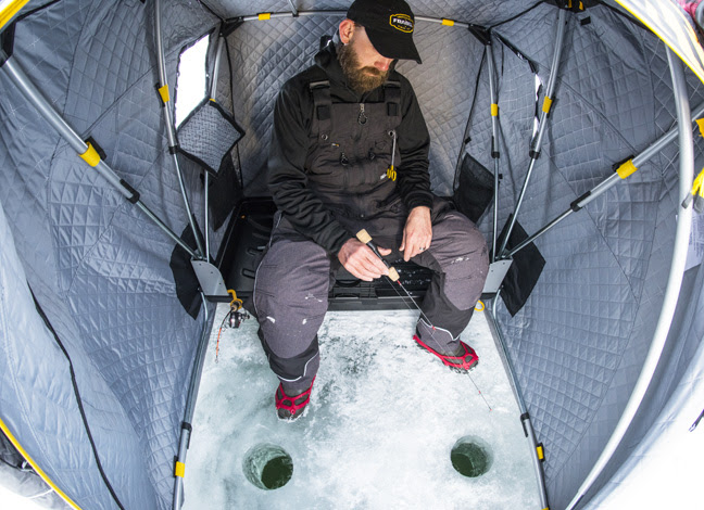 Рыбак в палатке с удочками