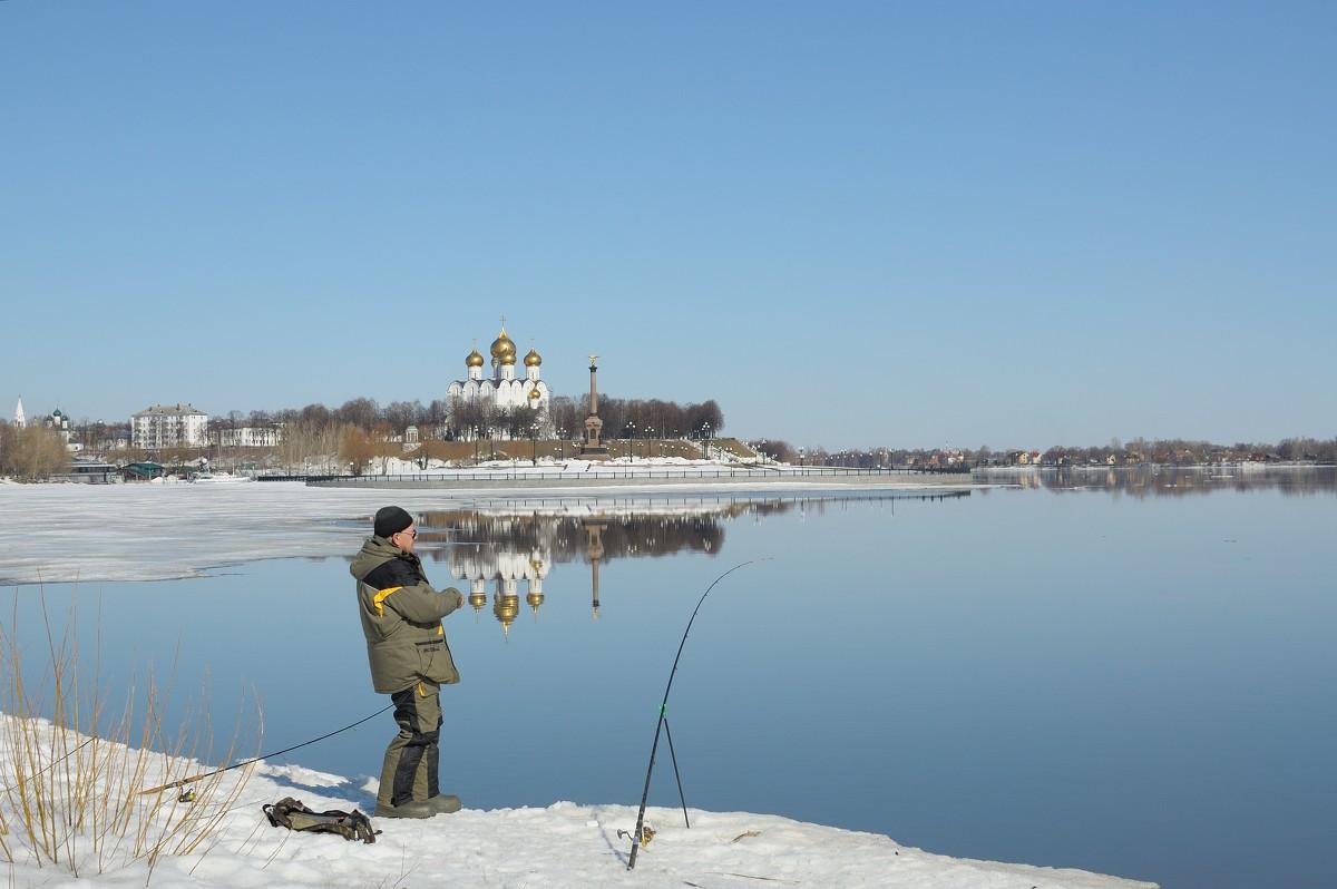 Мужик с удочками на берегу озера с прекрасным пейзажем