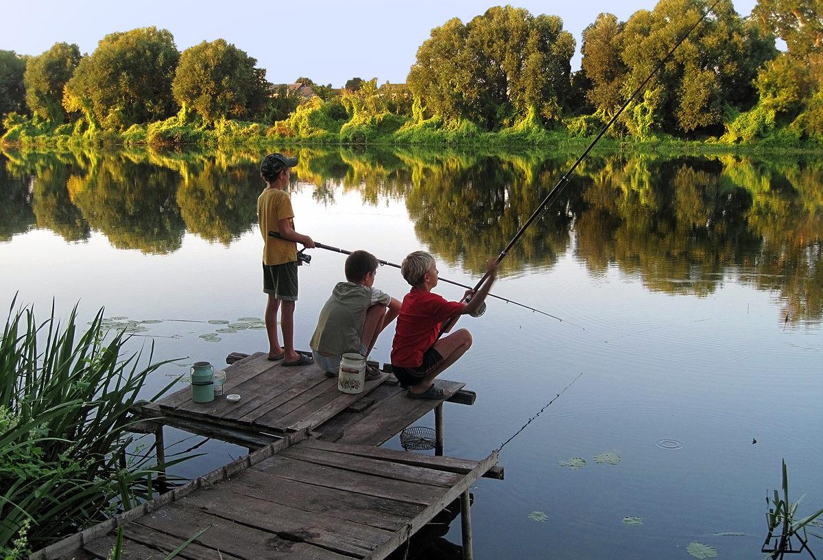 Трое юных рыбаков на пристани с удочками