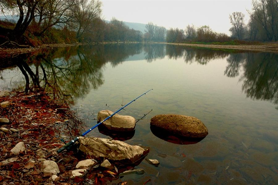 Удочка лежит на камнях прекрасного озера
