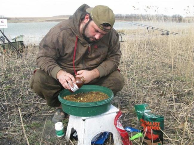 Рыбак готовит прикормку для карпа