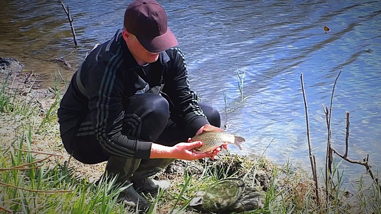 Рыбак на берегу озера с рыбай в руках