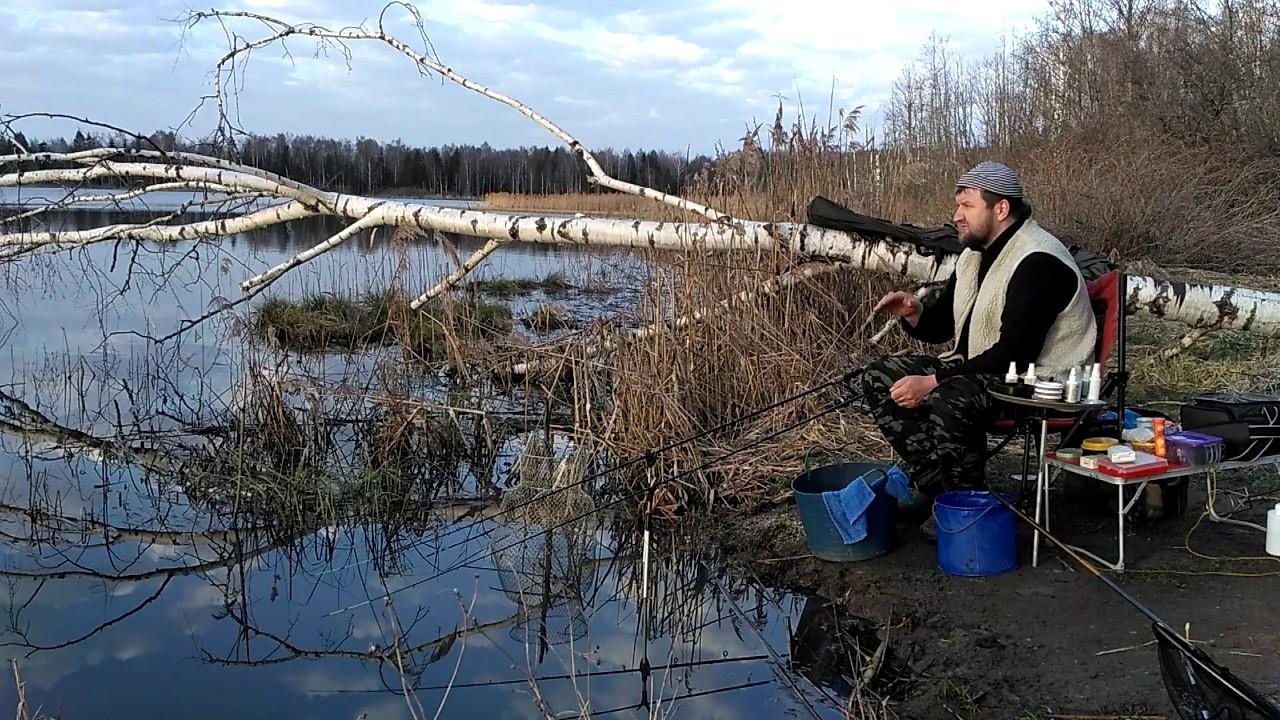 Рыбак на берегу озера с удочками