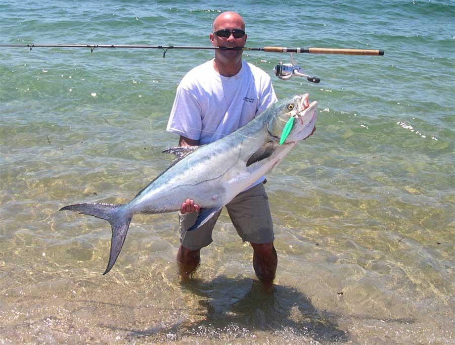 Лысый рыбак с огромной пойманной рыбиной