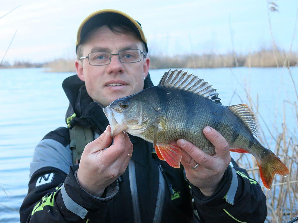 Рыбак с пойманной рыбай в руках
