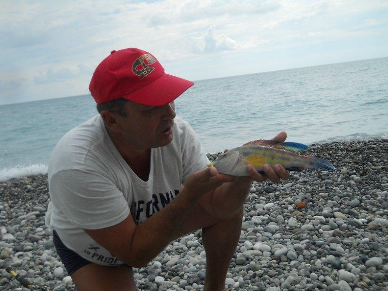 Мужик с пойманной рыбай в руках