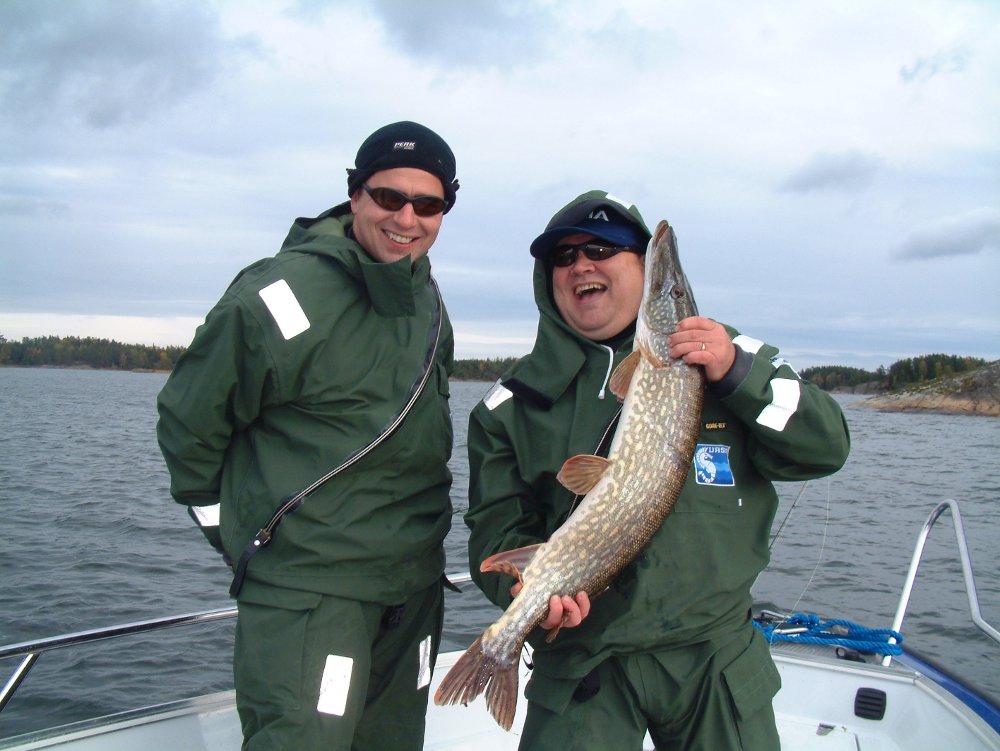 Два довольных рыбака с крупной щукой в руках