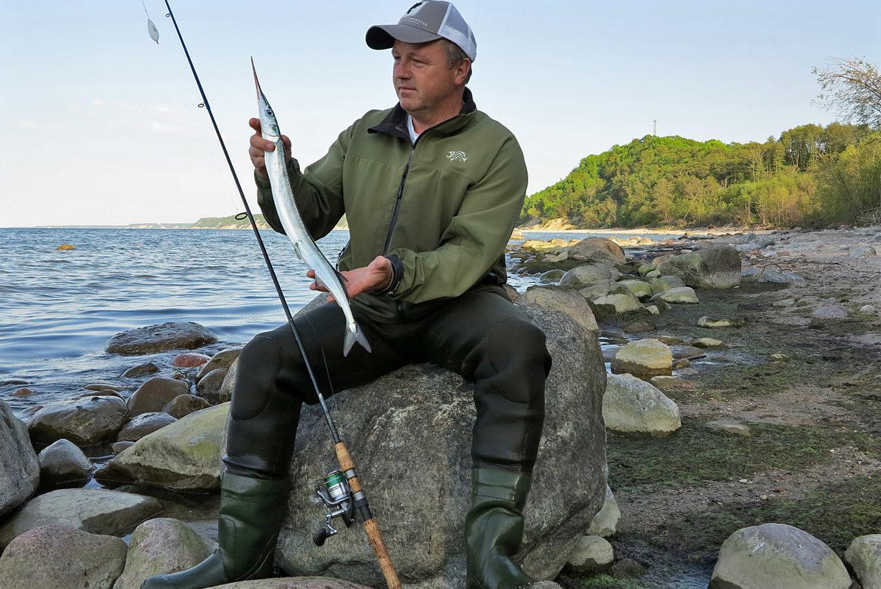 Рыбак с удочкой и пойманным сарганом