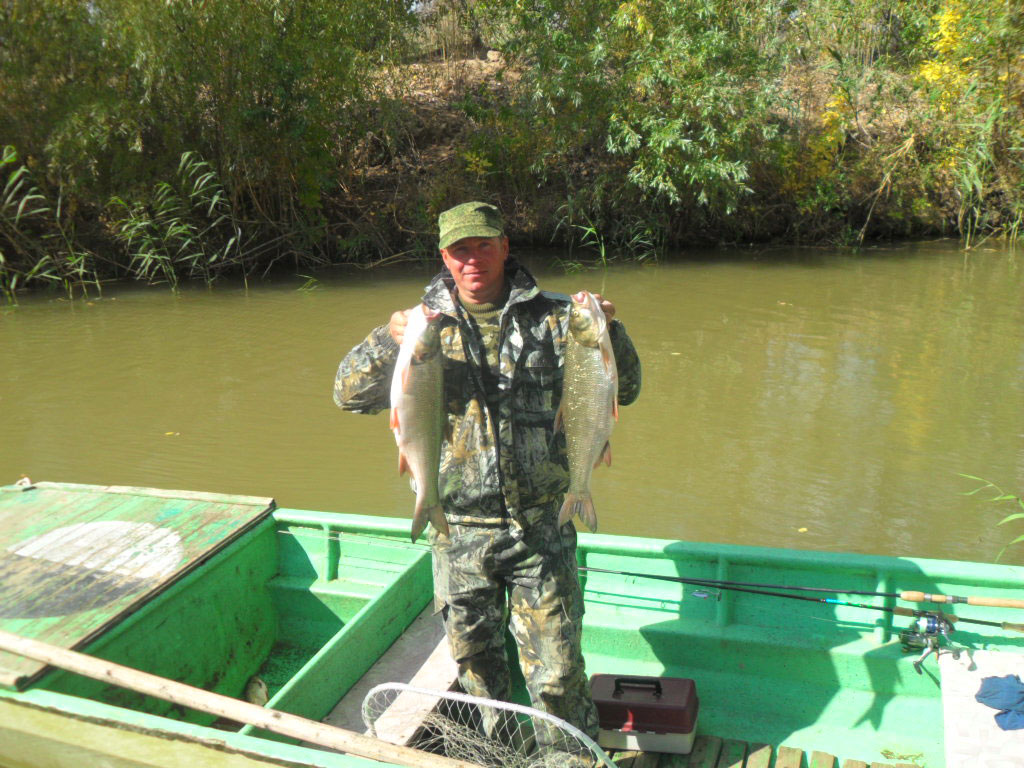 Рыбак в лодке с двумя рыбами в руках