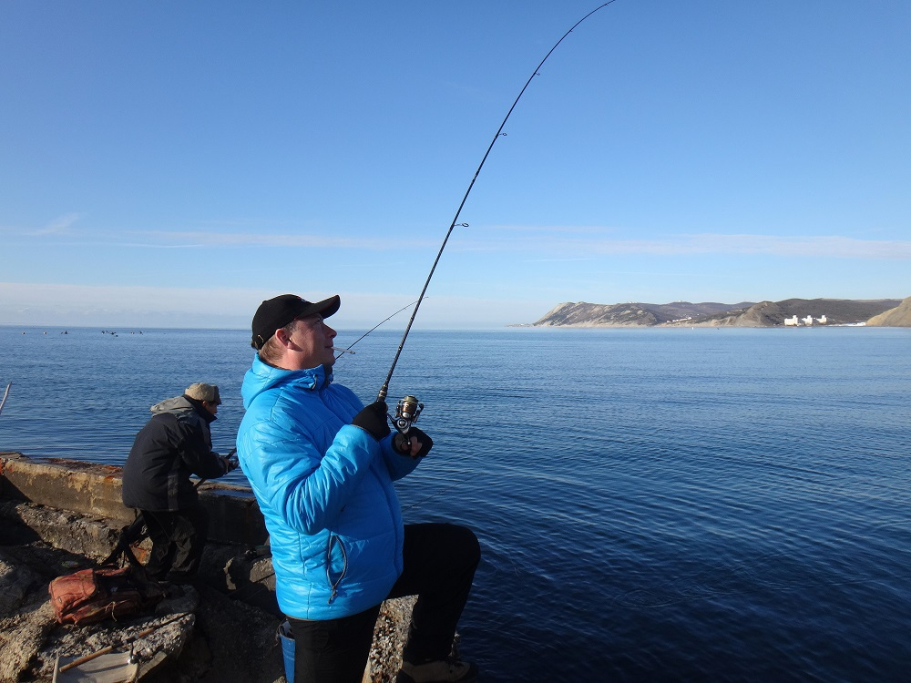 Рыбак в синей куртке со спиннингом