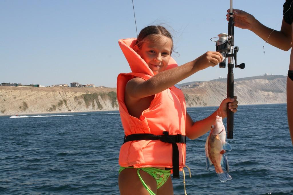 Юная рыбачка с удочкой в руках