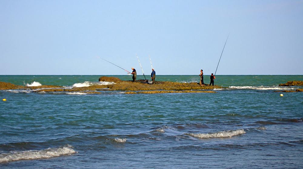 Четверо рыбаков на рифе с удочками
