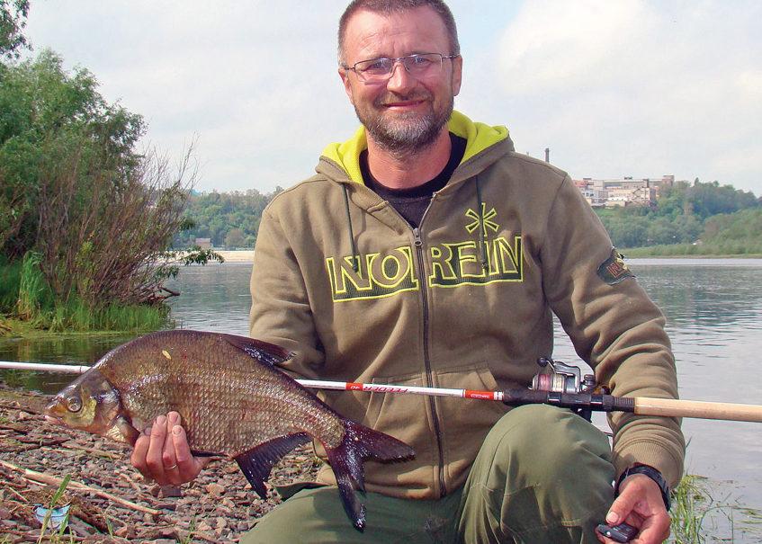 Довольный рыбак с пойманной рыбай в руке