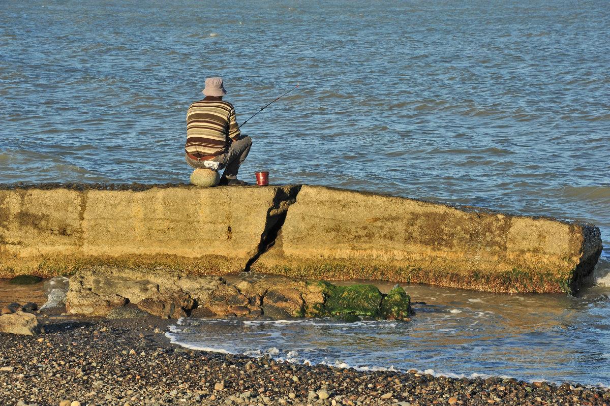 Одинокий рыбак на камне с удочкой