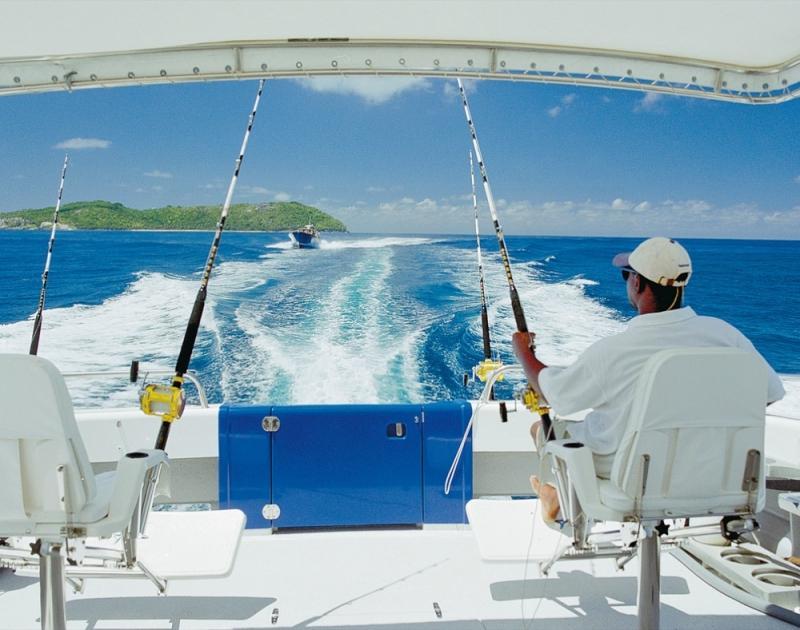 Рыбак на яхте с удочками