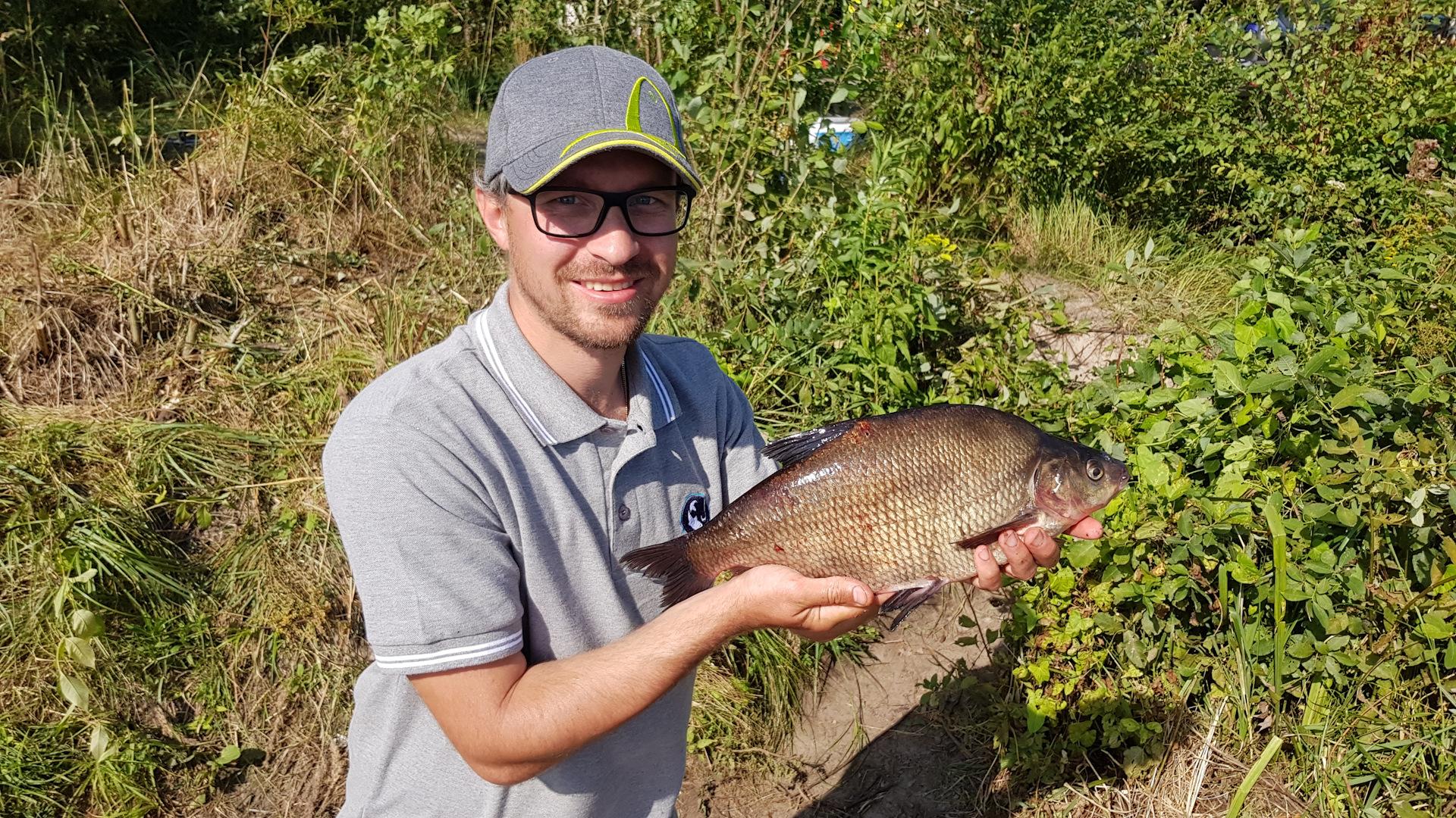 Парень в очка с пойманной рыбай в руках