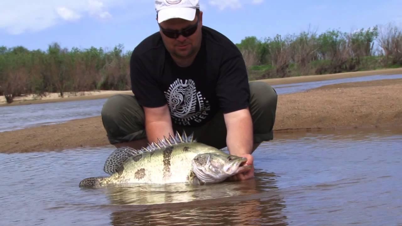 Рыболов с пойманной рыбиной в руках