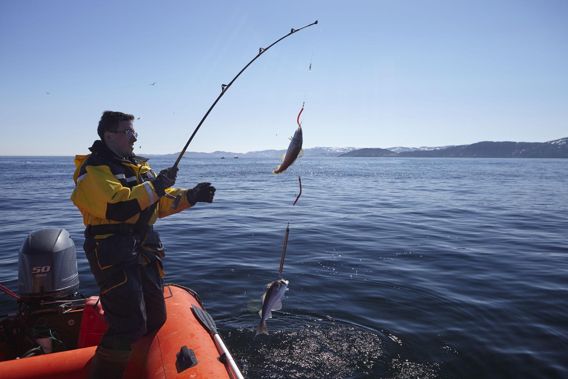 Рыбак в лодке с удочкой в руках