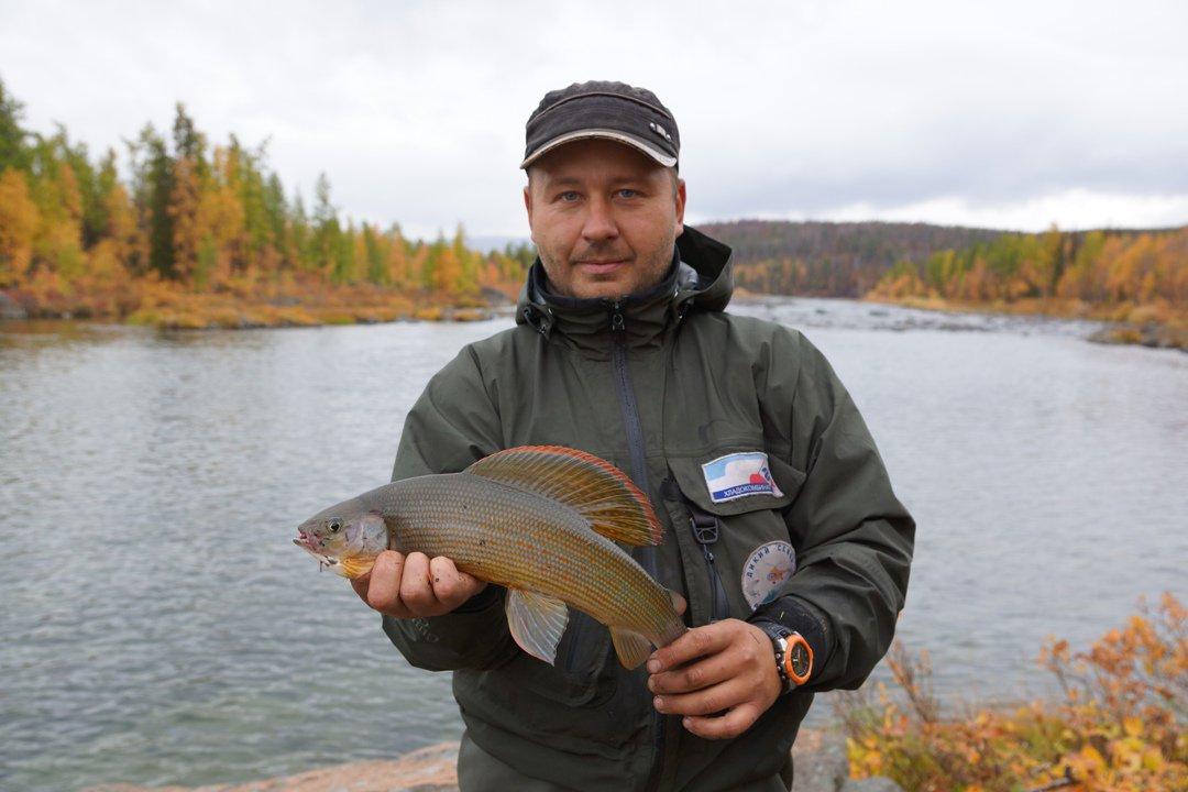Мужик на фоне реки с рыбой в руках