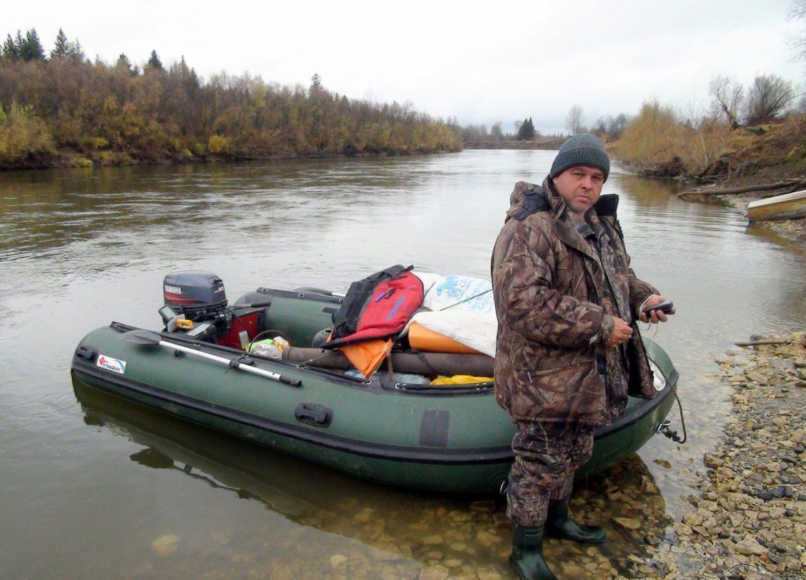 Мужик на берегу реки с надувной моторной лодкой