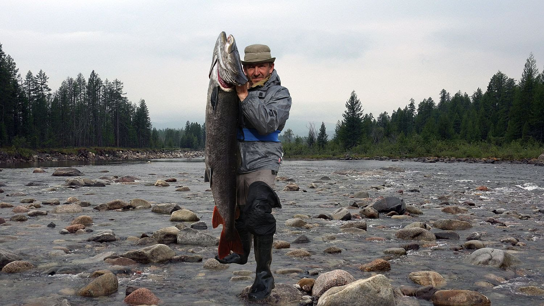 Мужик с крупной рыбой в руках