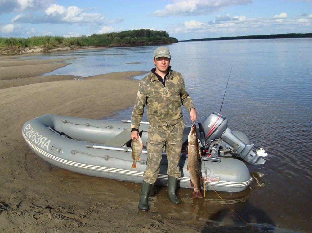 Рыбак у моторной лодки на фоне речки