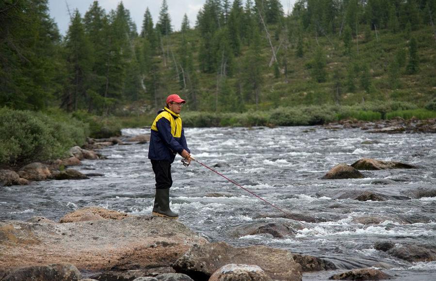 Рыбак с удочкой в руках на берегу реки