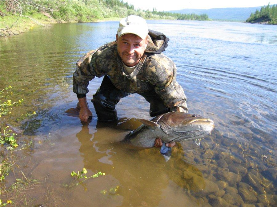 Довольный рыбак с крупной выловленной рыбой