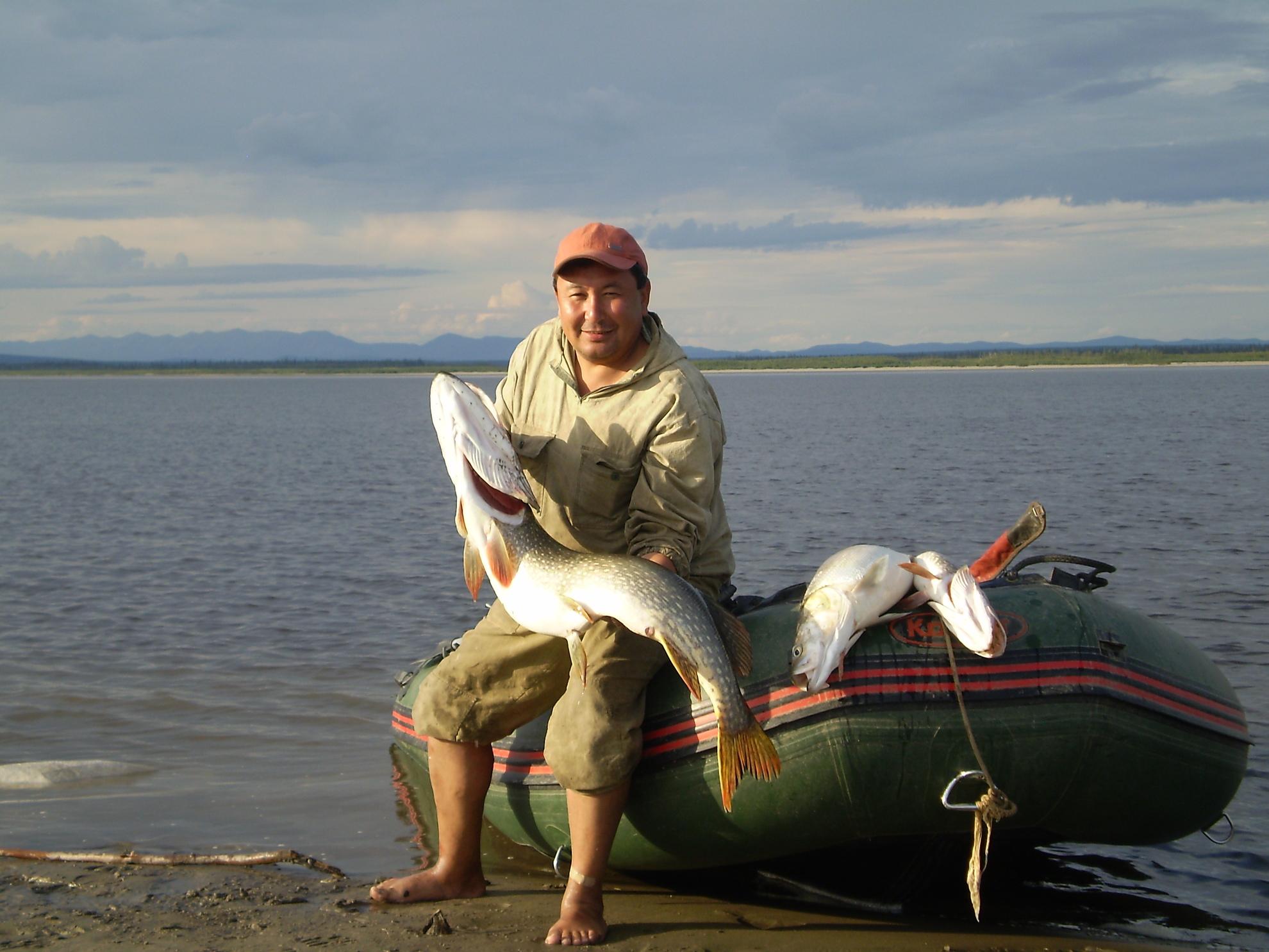 Рыбак рядом с лодкой с огромной щукой