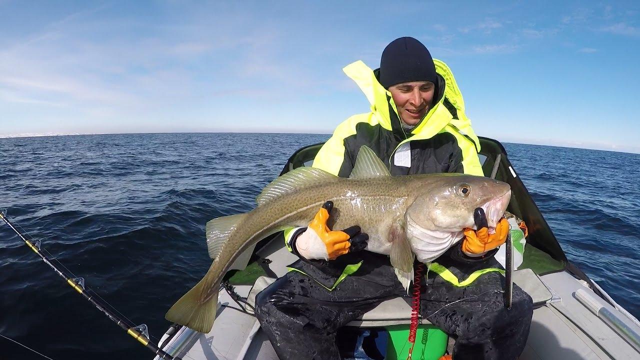 Довольный рыбак в лодке с отличным трофеем