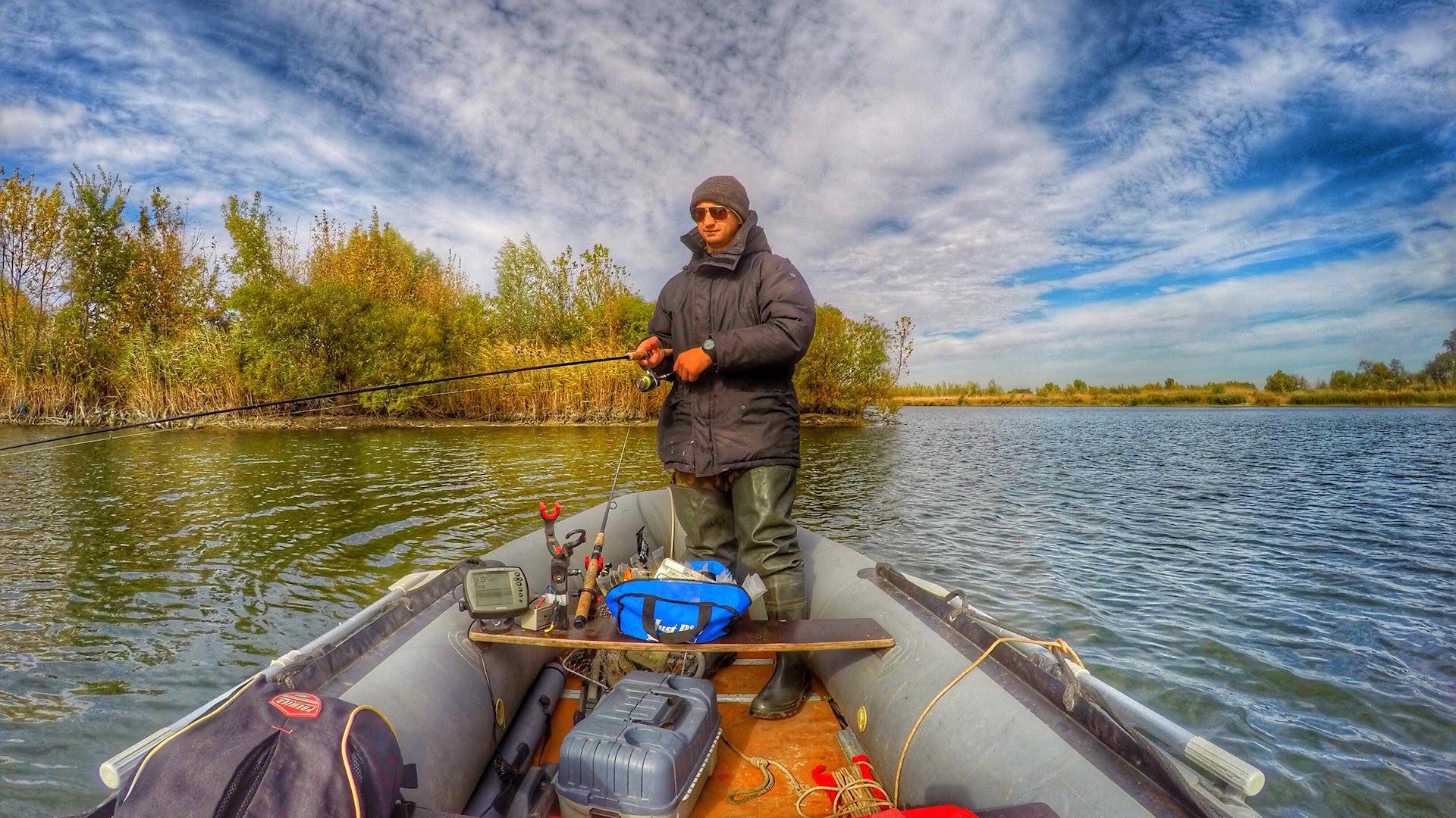 Рыбак стоя в лодке с удочкой в руках