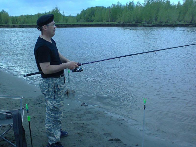 Мужик в черном берете с удочкой на берегу речки