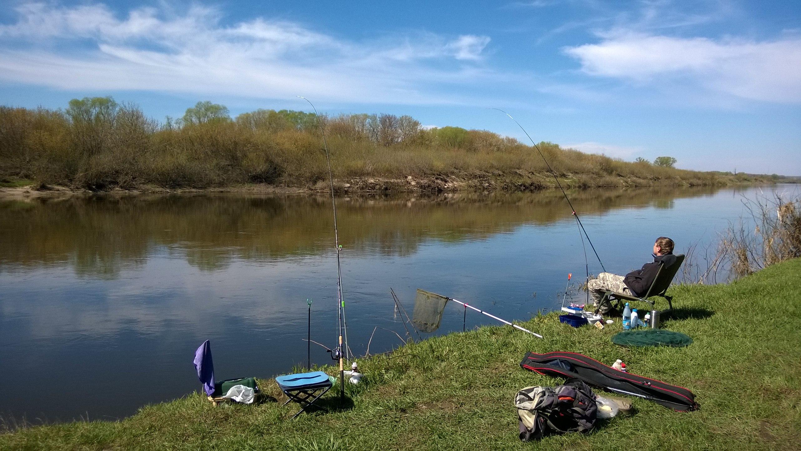 Рыбак в кресли на берегу реки
