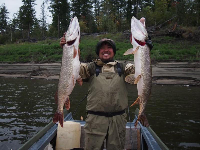 Рыбак в лодки с двумя огромными щуками