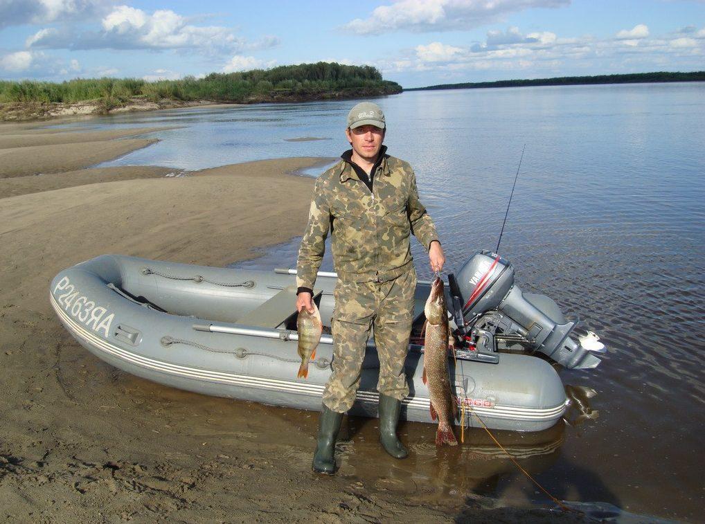 Рыбак и надувная моторная лодка на берегу реки